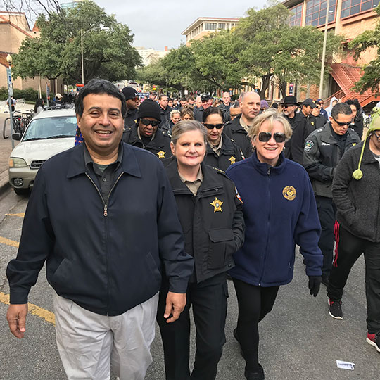 : TCDA Margaret Moore marching in the MLK Day parade with Sheriff Sally Hernandez, Travis County Attorney David Escamilla, and other members of law enforcement